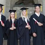 Smiling graduates posing — Stock Photo
