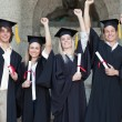 Smiling graduates posing while raising arms — Stock Photo