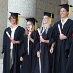 Smiling graduates posing while holding their diploma — Stock Photo