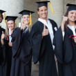 Graduates posing the thumb-up — Stock Photo