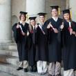 Five happy graduates posing the thumb-up — Stock Photo