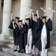 Five happy graduates posing the arms raised — Stock Photo