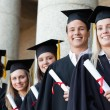 Close-up of five smiling graduates posing — Stock Photo