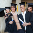 Close-up of a female graduate taking a picture of her friend — Stock Photo