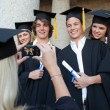 Close-up of a blonde graduate taking a picture of her friend — Stock Photo