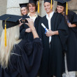 Stock Photo: Blonde graduate taking a picture of her friend