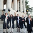 Stock Photo: Five happy grad students raising their hats