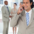 Businessman using a cell phone while his team is talking behind — Stock Photo