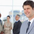 Smiling businessman standing upright with his team between him — Stock Photo