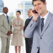 Smiling businessman using a mobile phone in front of his team — Stock Photo #13908539