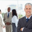 Mature smiling manager crossing his arms in front of his team — Stock Photo #13908662