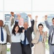 Smiling business team standing upright with arms raised in succe — Stock Photo #13908680