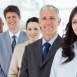 Four smiling employees standing upright around their director — Stock Photo