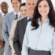 Confident and smiling manager standing among his employees — Stock Photo