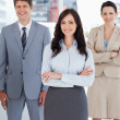 Young businesswomcrossing her arms in front of two relaxed co — Stock Photo #13908878
