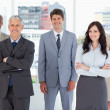 Foto Stock: Smiling executive standing in middle of bright room amon