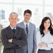 Five business crossing their arms in front of a bright wi — Stock Photo #13908893