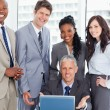 Smiling business team standing behind their director and the lap — Stock Photo
