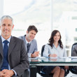 Royalty-Free Stock Photo: Mature manager sitting in front of his team with his hands his c
