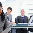 Serious businesswoman sitting in front of her team while smiling — Stock Photo #13909128