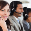 Smiling employee working with a headset while looking at the cam — Stock Photo
