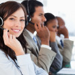 Stock Photo: Smiling call centre agent looking at camerwhile working ha