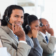 Stock Photo: Young call centre employee working among his team