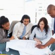 Stock Photo: Young business team working with flipchart sheets