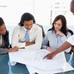 Young executive explaining an idea using flipchart sheets to co- — Stock Photo
