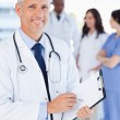 Stockfoto: Mature doctor showing beaming smile while pointing to somethin