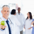 Mature doctor holding a green apple — Stock Photo