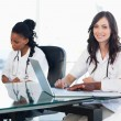 Two members of a medical team looking at the camera while workin — Stock Photo #13909667