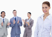 Close-up of a woman smiling with business applauding whil — Stock Photo