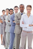 Serious workmates dressed in suits crossing their arms in a sing — Stock Photo
