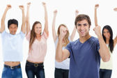 Man clenching his fists with behind him raising their arm — Stock Photo