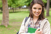 Portrait of a first-year student holding a textbook — Stock Photo