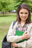 Portrait of a cute first-year student holding a textbook — Stock Photo