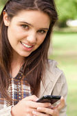 Portrait of a cute teenager using a smartphone — Stock Photo