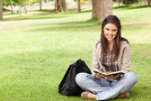 Smiling teenager sitting while holding a textbook — Stock Photo