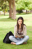 Teenager sitting with a textbook — Stock Photo