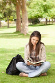 Teenager sitting while reading a textbook — Stock Photo
