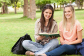 Female teenagers sitting with a textbook — Stock Photo