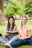 Portrait of female teenagers sitting with a textbook — Stock Photo
