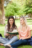 Two teenagers sitting with a textbook — Stock Photo