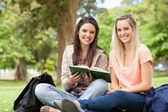 Smiling teenagers sitting while studying with a textbook — Stock Photo