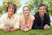 Portrait of three smiling students in a park — Stock Photo