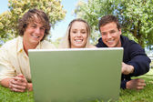 Portrait of three happy students in a park — Stock Photo