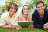 Three smiling students using a tactile tablet — Stock Photo