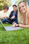 Close-up of a girl using a laptop while lying in a park — Stock Photo