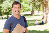 Portrait of a student smiling while holding a textbook — Stock Photo